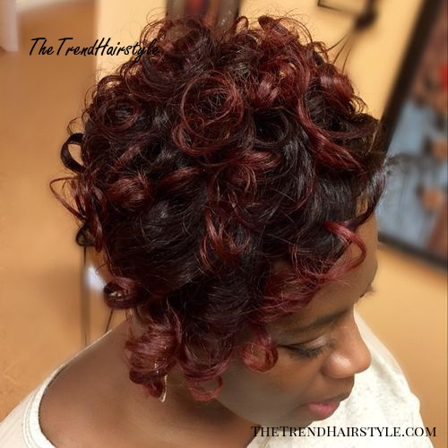 short curly black hairstyle with burgundy highlights